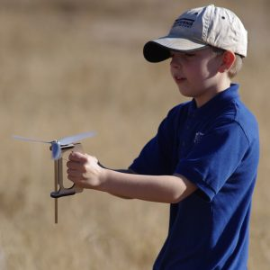 A young man prepares to launch a stick-helicopter.